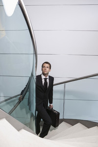 Businessman with briefcase looking up ascending spiral staircase