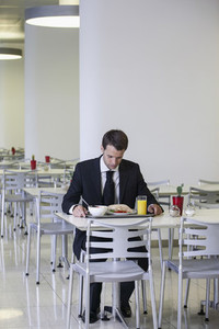 Businessman looking down at lunch tray in office cafeteria