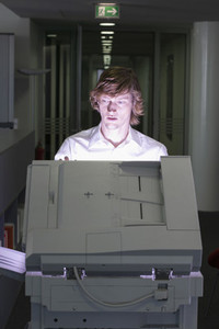 Young businessman using photocopier in office