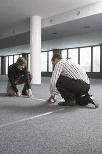 Businessmen measuring and marking floor in new office