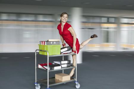 Portrait playful happy businesswoman riding office cart