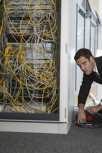Portrait suspicious businessman unplugging network server plug