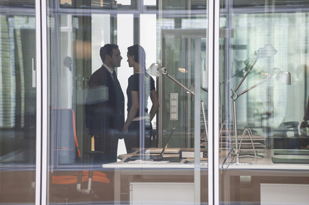Businessman and businesswoman face to face in office