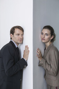 Portrait businessman and businesswoman at office wall corner