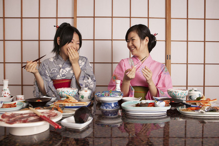 Happy young women in kimonos eating dinner in restaurant