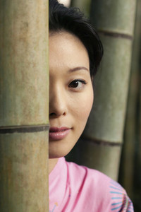 Close up portrait beautiful young Asian woman behind bamboo