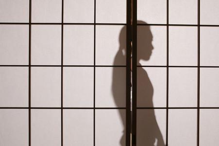 Shadow of young woman behind shoji sliding doors