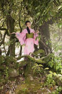 Portrait beautiful young woman in pink kimono below tree