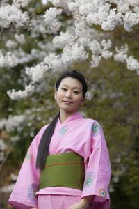 Portrait beautiful young woman in kimono below cherry blossoms