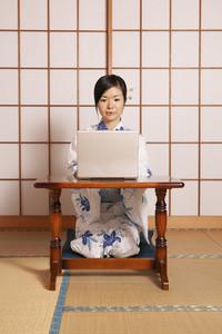 Young woman in kimono working at laptop at shoji door
