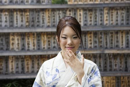 Beautiful young woman in kimono at Japanese prayer boards