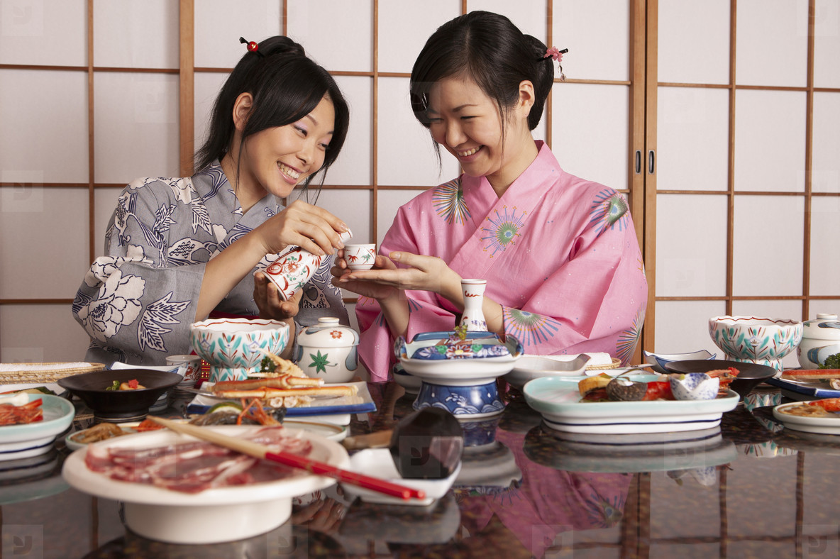 Happy young Japanese women in kimonos drinking tea with lunch
