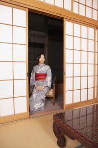 Serene young Japanese woman in kimono at shoji doorway