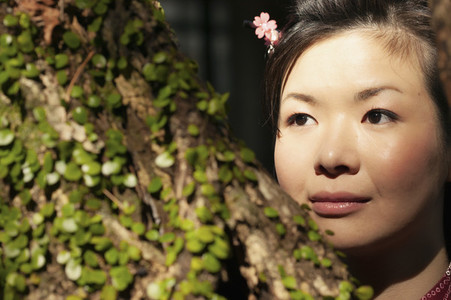 Close up portrait beautiful young woman looking away behind tree