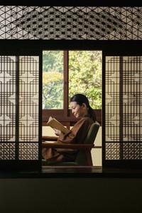 Young woman reading book in ornate shoji doorway
