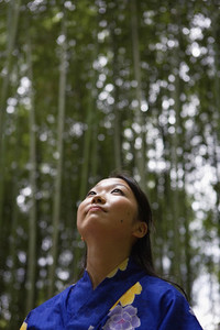 Thoughtful young woman in kimono looking up at bamboo trees