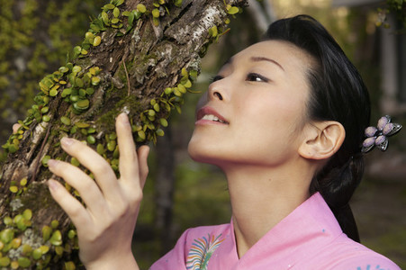 Beautiful young woman looking at buds growing on tree