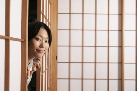 Portrait beautiful young woman peering from behind shoji doors