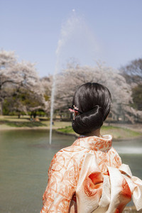 Young woman in orange kimono watching fountain in sunny Spring park