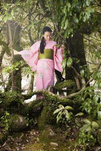 Young woman in pink kimono among beautiful trees