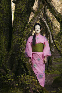 Portrait young woman in pink kimono in Japanese Noh mask at tree