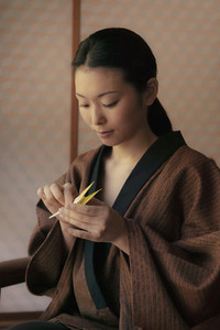 Beautiful young woman in robe making origami paper crane