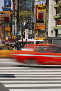 Cars speeding over crosswalk in sunny city Tokyo Japan