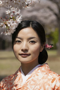 Close up portrait beautiful young woman below cherry blossoms