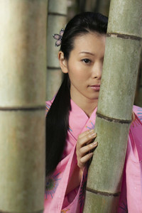 Portrait beautiful young woman in pink kimono at bamboo trees