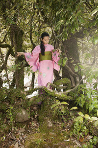 Beautiful young woman in pink kimono below trees