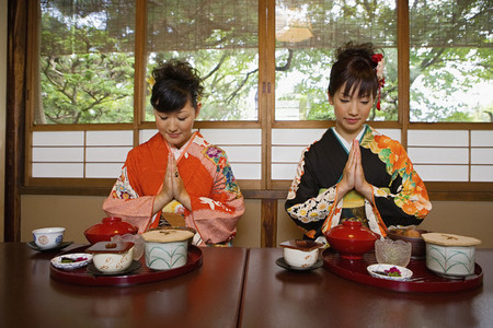 Young women in kimonos praying over lunch in restaurant