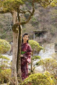 Beautiful young woman in Japanese kimono at tree in tranquil park
