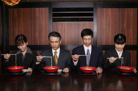 Japanese business people in suits eating ramen with chopsticks