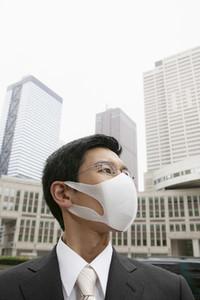 Portrait businessman in face mask below city highrise buildings