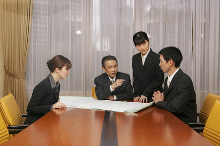 Business people discussing blueprints in office conference room