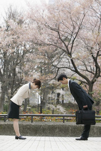 Japanese business people bowing to each other in park