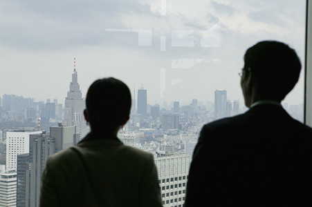 Business people looking at cityscape from highrise office window