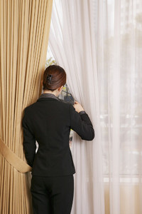 Businesswoman looking out window between curtains