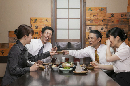 Happy Japanese business people enjoying sushi lunch in restaurant