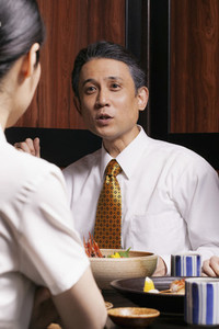 Businessman talking to colleague at lunch in restaurant