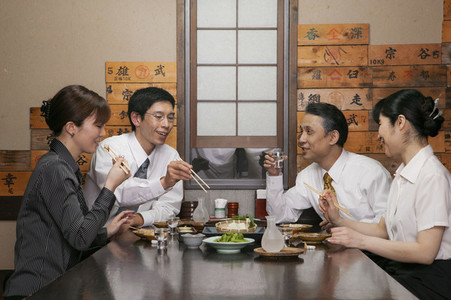 Japanese business people eating lunch at restaurant table