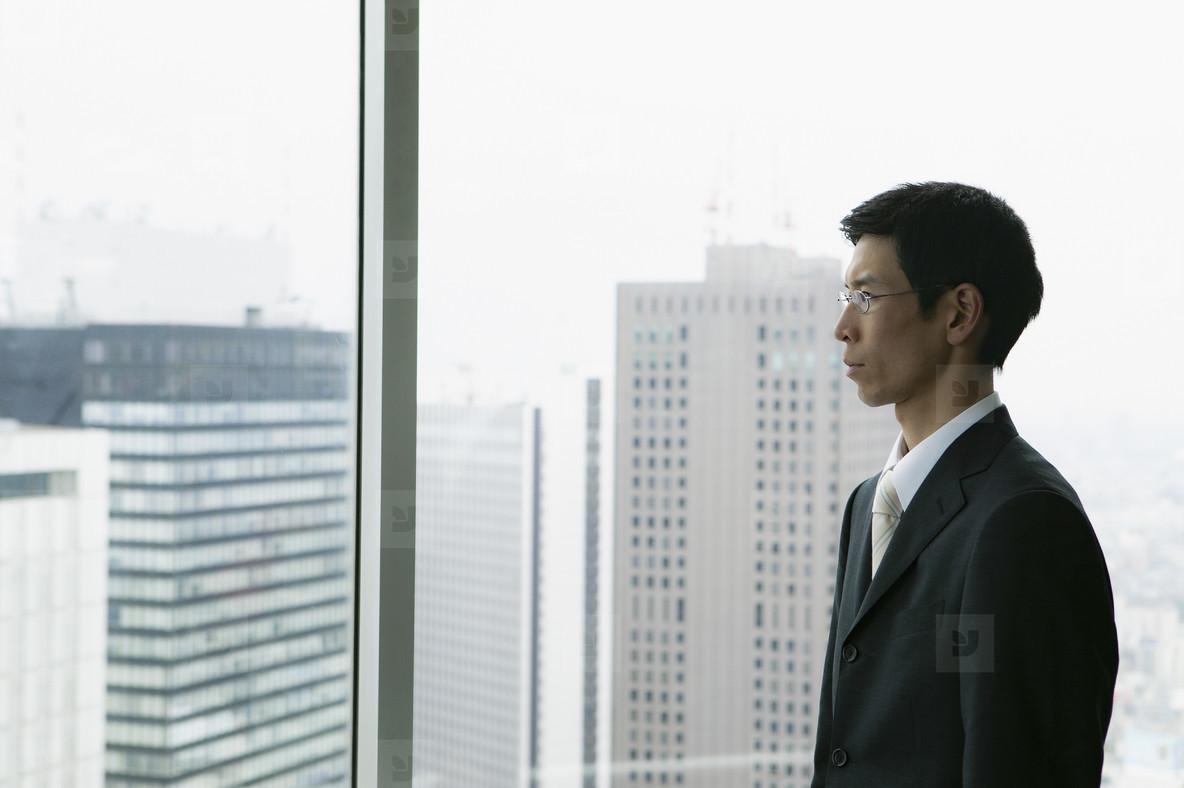 Businessman looking out urban highrise office window