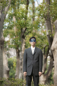 Blindfolded businessman in park with trees