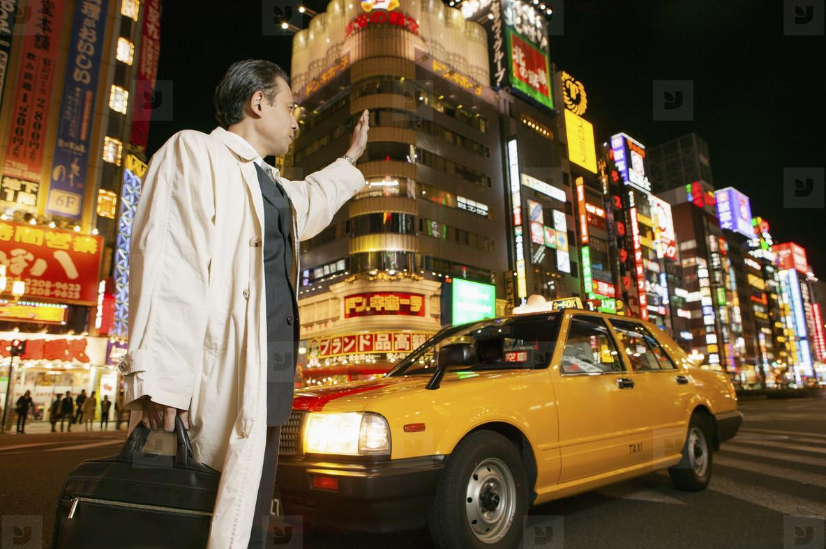 Businessman hailing taxi on city street Tokyo Shinjuku Japan