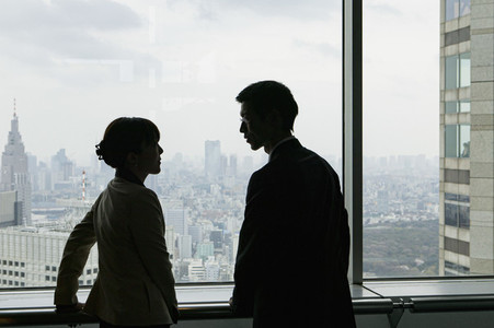 Business people talking at urban highrise office window