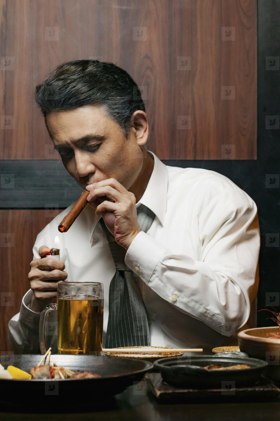 Businessman lighting cigar at restaurant table
