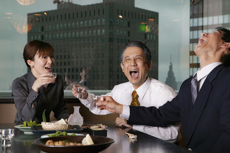 Happy business people laughing at lunch in highrise restaurant
