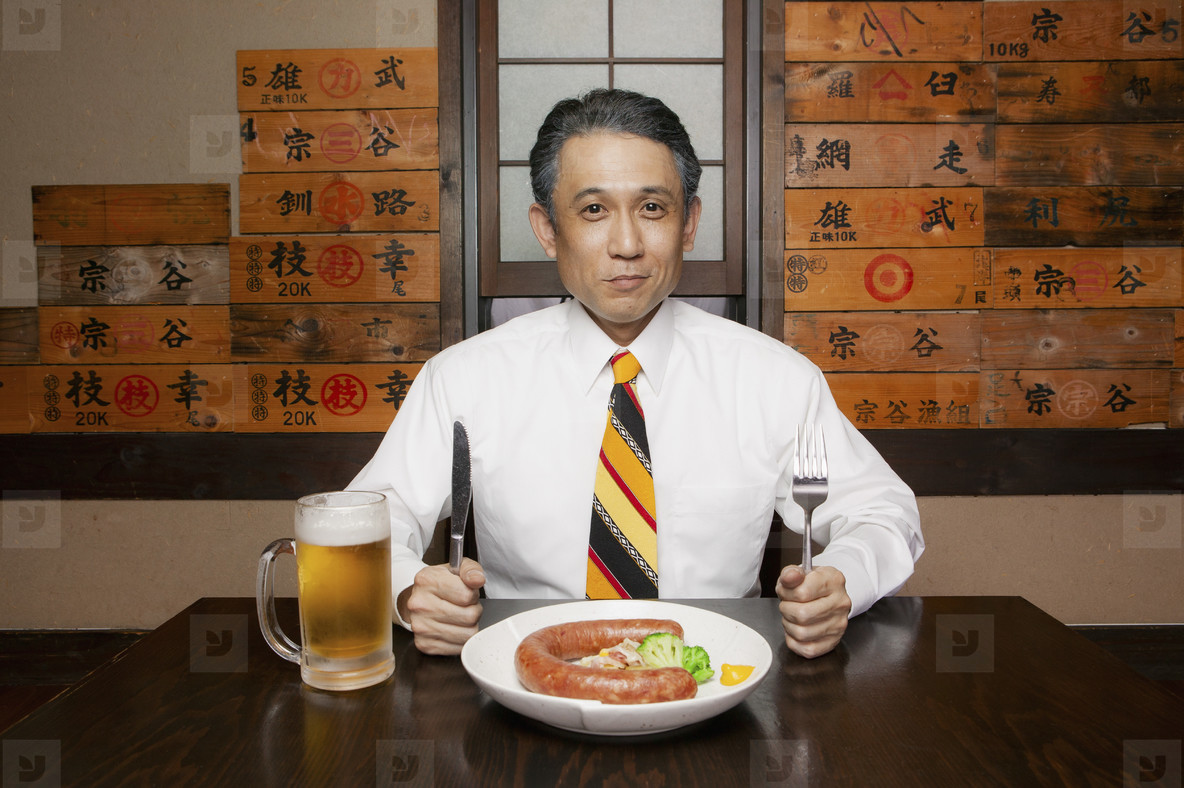 Portrait hungry businessman with sausage and beer in restaurant