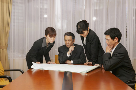 Business people reviewing blueprints in office conference room