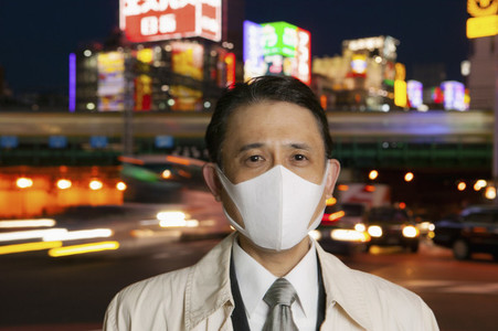 Portrait confident businessman in face mask in city at night Tokyo Japan